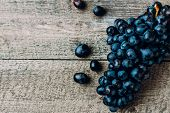 Bunches Of Fresh Ripe Red Grapes On A Wooden Textural Table Background. Dark Grapes, Blue Grapes, Wi poster