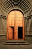 stock photo of centenarian  - wood and golden gate to enter gothic cathedral of Arucas in the Canary Islands - JPG