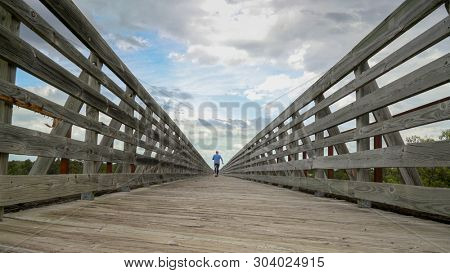 poster of senior man is walking on a long trestle over Long Pine Creek -  recreational Cowboy Trail in norther
