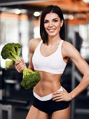 Diet And Weight Loss Concept. Sporty Woman Fitness Instructor Recommends Proper Nutrition Holding Bi poster