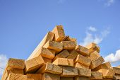 Stacked Lumber On Blue Sky.folded Wood.closeup Wooden Boards.the Surface Of The End Of The Board.lot poster