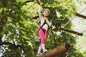 Child Playing On The Playground. Children Fun. Hiking In The Rope Park Girl In Safety Equipment. Hig poster
