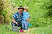 Boy And Father In Nature With Watering Can. Spring Garden. Dad Teaching Little Son Care Plants. Litt poster