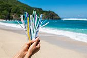 Hand Holding Heap Of Used Plastic Straws On Background Of Clean Beach And Ocean Waves. Plastic Ocean poster