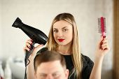Blonde Hairstylist Showing Blow Dryer And Comb. Woman Hairstylist Using Hairbrush And Hairdryer For  poster