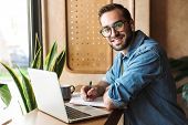 Photo of attractive smiling man wearing glasses writing and using earpod with laptop while working i poster
