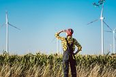 Farmer woman has invested not only in land but also wind energy watching the turbines poster
