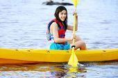 foto of biracial  - Biracial Teen girl paddling yellow kayak on lake - JPG