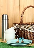 metal thermos with cups, plates and basket on grass on wooden background