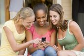 image of mobile-phone  - Teenage Girls Sitting Outside Playing With Mobile Phone - JPG