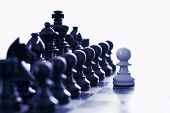 image of chess piece  - White pawn challenging army of black chess pieces blue tone - JPG