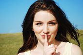 stock photo of shh  - Beautiful young woman saying shh with a finger to her lips outdoors - JPG