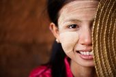 Portrait of beautiful shy young traditional Myanmar girl with straw hat smiling. Close up head shot.