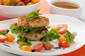 pic of crab-cakes  - Close up of crab cakes and cherry tomato salad appetizer garnished with basil and balsamic vinegar sauce - JPG