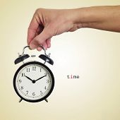 picture of wind up clock  - someone holding a typical mechanical alarm clock and the word time written in a beige background with a retro effect - JPG