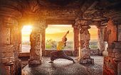 stock photo of hindu  - Woman doing yoga in ruined ancient temple with columns at sunset in Hampi Karnataka India - JPG