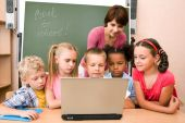 foto of school child  - Portrait of pupils looking at the laptop display with teacher near by - JPG