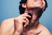 pic of razor  - Young Man is Shaving With Electric Razor - JPG