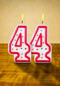 Burning birthday candles number 44 on a wooden background