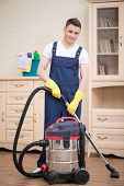 stock photo of wet t-shirt  - Selective focus on young smiling dark-haired janitor wearing white T-shirt overalls and yellow rubber gloves vacuuming in the office. Working place on background