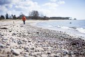 picture of stroll  - Woman strolling along the beachside in bright light - JPG