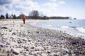 foto of stroll  - Woman strolling along the beachside in bright light - JPG