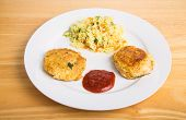 foto of crab-cakes  - Two browned crab cakes in white plate with cocktail sauce and vegetable rice - JPG