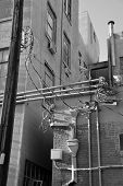 picture of osha  - An urban alley shows electronic and electrical modifications made over the years resulting in a tangle of exposed conduit - JPG