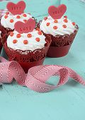 pic of red velvet cake  - Happy Valentine red velvet cupcakes with love messages on green teal blue sixties style vintage wood background - JPG