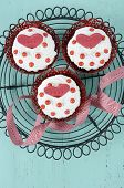 stock photo of red velvet cake  - Happy Valentine red velvet cupcakes with love messages on vintage baking rack on green teal blue sixties style vintage wood background  - JPG