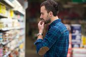stock photo of grocery store  - Handsome Young Man Shopping For Fruits And Vegetables In Produce Department Of A Grocery Store - Supermarket - Shallow Deep Of Field