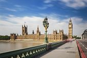 image of westminster bridge  - Long exposure of the Houses of Parliament in London with blue sky seen from the Westminster Bridge with some blurred people - JPG