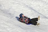 stock photo of snow-slide  - Happy child slides on a plastic board from a hill in winter - JPG