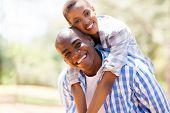 pic of piggyback ride  - pretty african woman enjoying piggyback ride on boyfriend outdoors - JPG