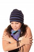 stock photo of freezing temperatures  - Girl wearing a wool hat and scarf but bare sleeves holding herself as if cold or freezing - JPG