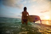 stock photo of board-walk  - Young lady surfer walking into the sea with board - JPG