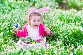 image of bunny ears  - Adorable curly toddler girl wearing bunny ears playing with Easter eggs in a white basket sitting in a sunny garden with first white spring flowers - JPG