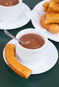 pic of churros  - spanish pastry - cup of chocolate with churros