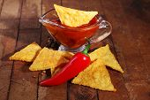 picture of nachos  - Tasty nachos and bowl with sauce on wooden background - JPG