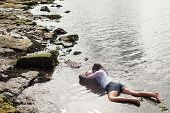 picture of accident victim  - View of a young woman washed up on rocks at the edge of a river possible boating accident victim - JPG