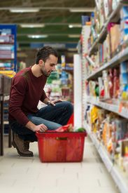 stock photo of department store  - Handsome Young Man Shopping For Fruits And Vegetables In Produce Department Of A Grocery Store  - JPG