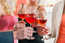 stock photo of shot glasses  - Close up Shot of Friends Tossing Glasses of Red Wine in a Party - JPG