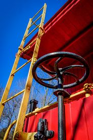pic of caboose  - Brightly painted caboose ladder and brake wheel against a blue sky - JPG