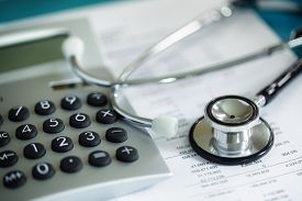 foto of stethoscope  - Calculator and stethoscope on financial statement concept for finance health check or cost of healthcare - JPG