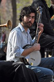 image of banjo  - New York USA - April 09 2008: A musician plays his banjo in a trad. jazz band for the lunch time crowds in Washington Square Greenwich Village. ** Note: Soft Focus at 100%, best at smaller sizes - JPG