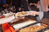 foto of catering  - Hands of cook serving food at a catered event - JPG