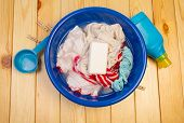 picture of dirty-laundry  - Dirty laundry in blue bowl with soap on wooden table - JPG