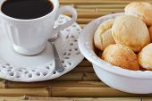 stock photo of brazilian food  - Brazilian snack pao de queijo (cheese bread) on white plate with cup of coffee on bamboo table. Selective focus ** Note: Shallow depth of field - JPG