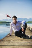 stock photo of pier a lake  - Handsome young man on a lake in a sunny - JPG