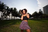 stock photo of jamaican  - Stock image of a Jamaican woman posing in fashionable clothing in the park - JPG